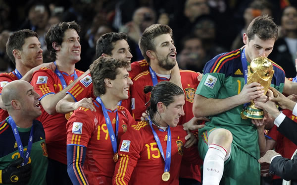 Spain goalkeeper Iker Casillas, right, kisses the World Cup trophy at the end of the World Cup final soccer match between the Netherlands and Spain at Soccer City in Johannesburg, South Africa, Sunday, July 11, 2010. (AP Photo/Martin Meissner)