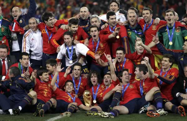 The Spanish team pose for photographers with the World Cup trophy, center foreground, following the World Cup final soccer match between the Netherlands and Spain at Soccer City in Johannesburg, South Africa, Sunday, July 11, 2010. Spain won 1-0. (AP Photo/Ivan Sekretarev)