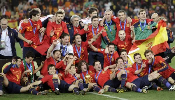 The Spanish team pose for photographers with the World Cup trophy, center foreground, following the World Cup final soccer match between the Netherlands and Spain at Soccer City in Johannesburg, South Africa, Sunday, July 11, 2010. Spain won 1-0. (AP Photo/Martin Meissner)
