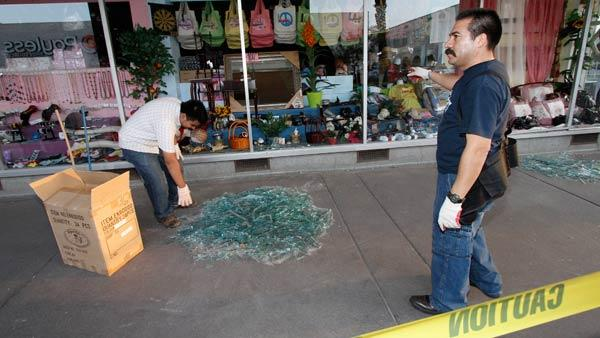 Men clean up broken glass from window store fronts in downtown Calexico, Calif. after an earthquake struck the area Sunday.