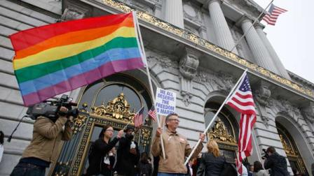 FILE - In this Aug. 12, 2010 file photo, Billy Bradford of Castro Valley, Calif., waves a pair of flags outside City Hall while same-sex couple line up to see if they can be married in San Francisco, Thursday, August 12, 2010.