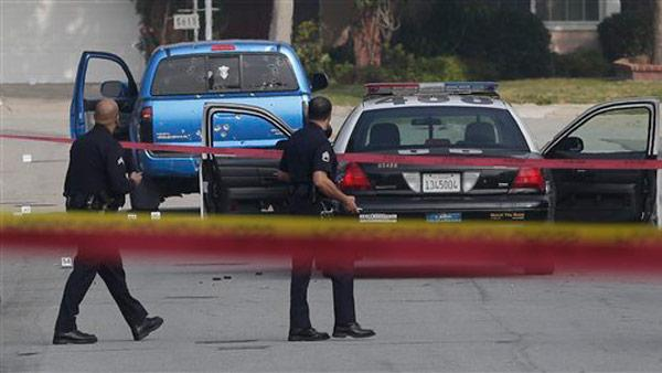 Law enforcement officers look over the scene of an officer involved shooting in Torrance, Calif., Thursday, Feb. 7, 2013. The shooting is believed to related to