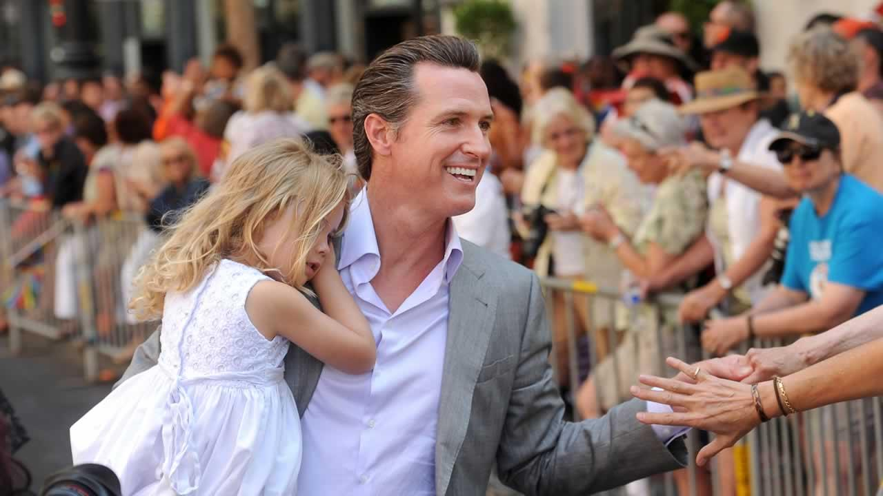 Holding his daughter Montana, California Lt. Gov. Gavin Newsom greets spectators during San Franciscos 43rd annual gay pride parade Sunday, June 30, 2013.