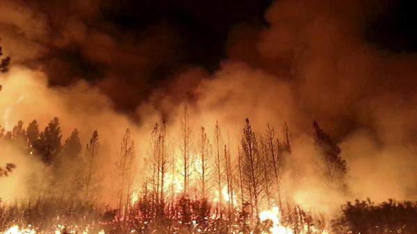 The wildfire outside Yosemite National Park  one of more than 50 major brush blazes burning across the western U.S.  more than tripled in size overnight and still threatens about 2,500 homes, hotels and camp buildings.