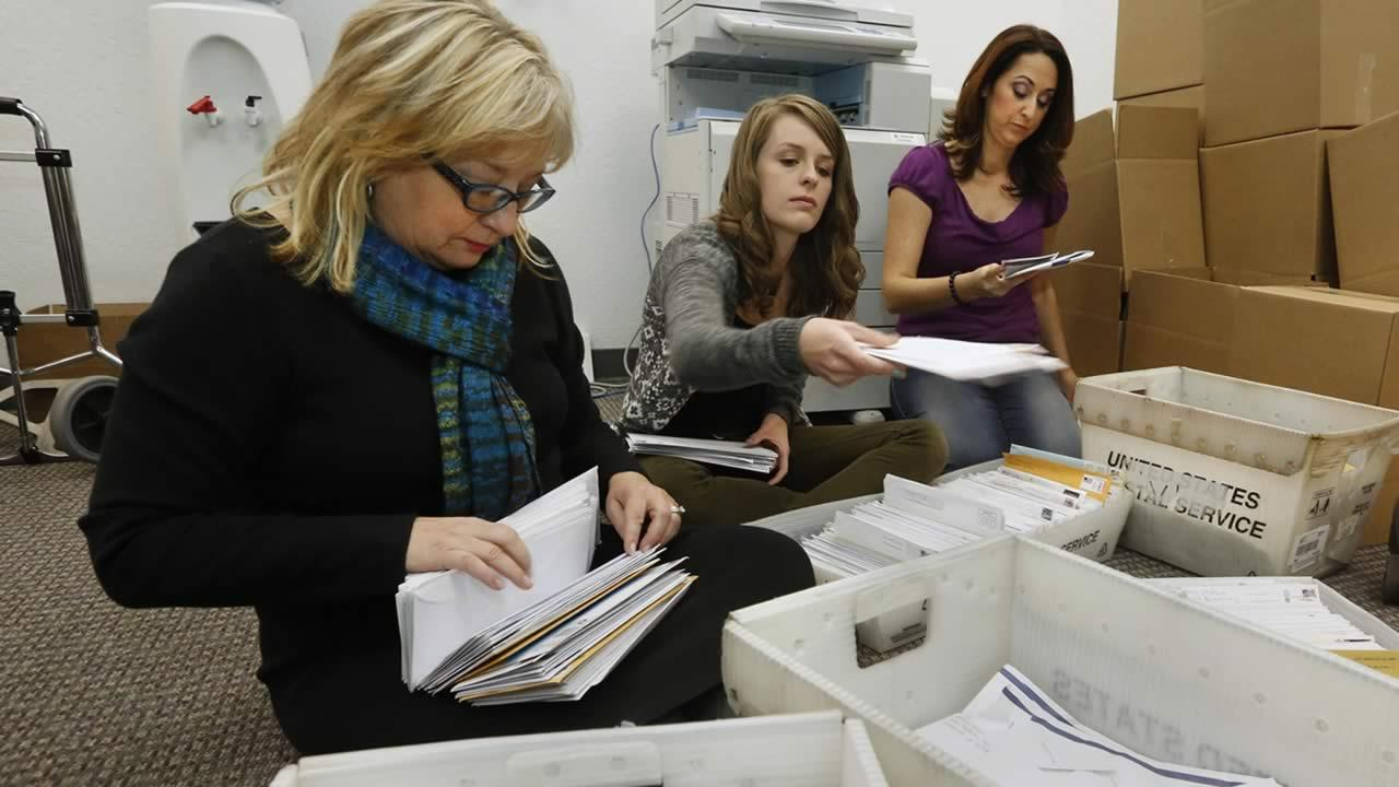 Karen England, executive director of the California Resource Institute, left, and volunteers Grace LeFever, center, and Christina Hill, sort through stacks of mail with petitions