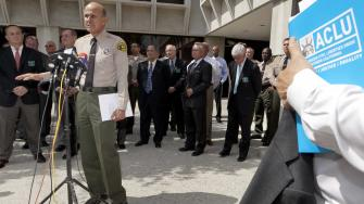 FILE - In this Sept. 28, 2011 file photo, Los Angeles County Sheriff Lee Baca, at podium, takes questions about a report released by the American Civil Liberties Union, ACLU, outside Sheriffs headquarters in Los Angeles