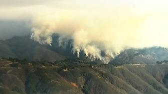 A wildfire burning in the Big Sur area of California destroyed at least 15 homes and forced about 100 people to evacuate.