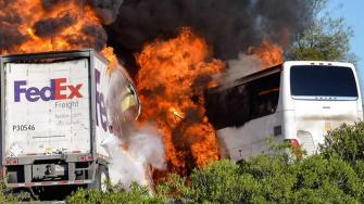 Massive flames engulf a tractor-trailer and a tour bus just after they collide on Interstate 5, Thursday April, 10, 2014, near Orland, Calif. At least 10 people were killed in the crash, authorities said