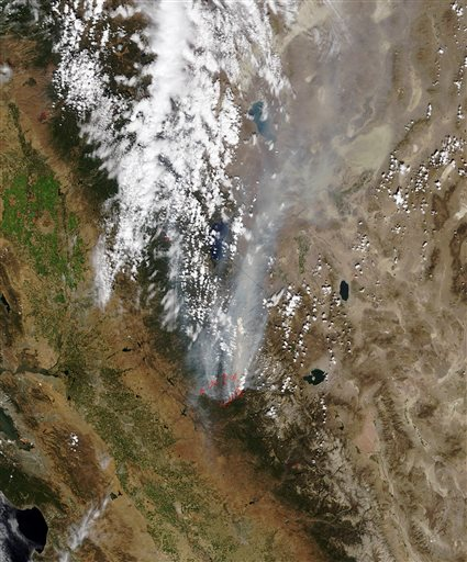 In this Monday, Aug. 26, 2013 satellite photo released by NASA, a smoke plume trails north from the drought-fueled Rim Fire, center, burning near Yosemite National Park in central California. Red outlines indicate hot spots where the satellite detected unusually warm surface temperatures associated with fires. Containment of the fire more than doubled to 15 percent, although it was within a mile of the park&#39;s Hetch Hetchy Reservoir, the source of San Francisco&#39;s famously pure drinking water, officials said. <span class=meta>(AP Photo&#47;NASA)</span>