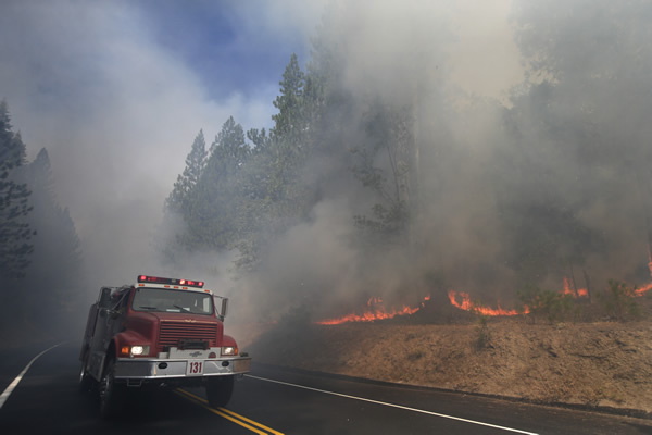 A fire truck drives past burning trees as firefighters continue to battle the Rim Fire near Yosemite National Park, Calif., on Monday, Aug. 26, 2013