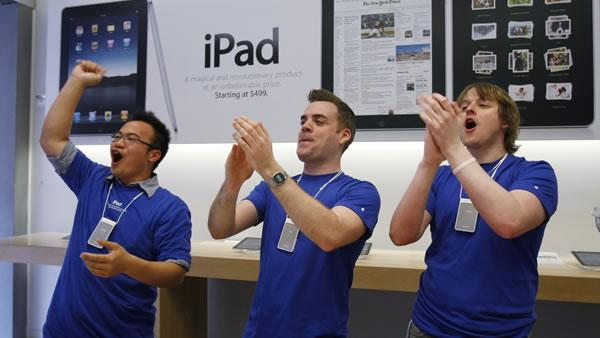 Three Apple workers cheer as the first customers buy an Apple iPad on the first day of iPad sales at an Apple Store in San