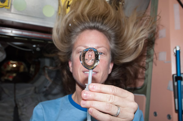 NASA astronaut Karen Nyberg, Expedition 36 Flight Engineer, squeezes a water bubble out of her beverage container, showing her image refracted, in the Unity node of the International Space Station. <span class=meta>(NASA)</span>