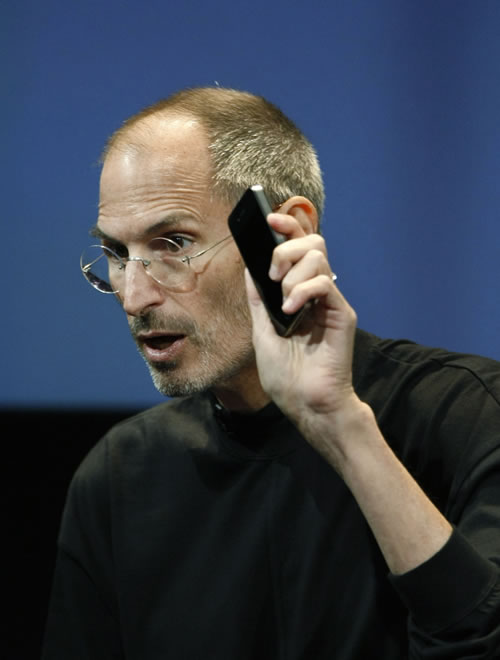 Apple CEO Steve Jobs holds up iPhone 4 as he talks about the Apple iPhone 4 at Apple headquarters in Cupertino, Calif., Friday, July 16, 2010. (AP Photo/Paul Sakuma)