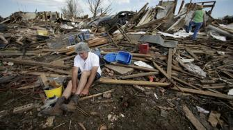 Rick Brown puts on a pair of boots after finding them in his tornado-ravaged home Wednesday, May 22, 2013, in Moore, Oklahoma