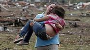 A woman carries her child through a field near the collapsed Plaza Towers Elementary School in Moore, Okla., Monday, May 20, 2013.