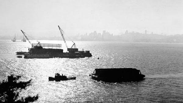 A tugboat towed a barge to be loaded with soil from the excavation on Yerba Buena Island in 1933.  (Photo courtesy baybridgeinfo.org)