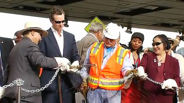 Lt. Governor Gavin Newsom cuts the ceremonial chain with a blow torch to mark the opening of the Bay Bridge.