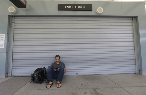 "<div class=""meta image-caption""><div class=""origin-logo origin-image ""><span></span></div><span class=""caption-text"">Bryan Maas waits for a CalTrain train in front of a closed Bay Area Rapid Transit ticket booth in Millbrae, Calif., Monday, July 1, 2013. Early Monday, July 1, 2013, two of San Francisco Bay Area Rapid Transit's (BART) largest unions went on strike after weekend talks with management failed to produce a new contract. Maas said he would normally ride BART from San Francisco International Airport but heard of the strike on Twitter. (AP Photo/Jeff Chiu)</span></div>"