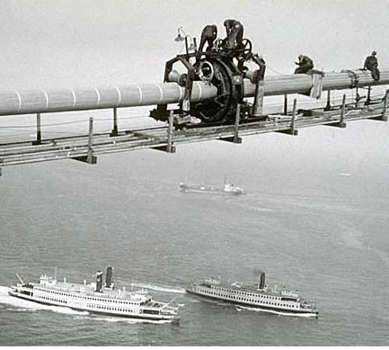 The actual cable spinning operation involved carrying wire from one anchorage to the next, over the tops of the towers. While it followed a predictable process, this operation was also among the most technically challenging, requiring the services of skilled workmen at nearly every juncture and subjecting the workmen to the greatest danger. (Photo courtesy baybridgeinfo.org)
