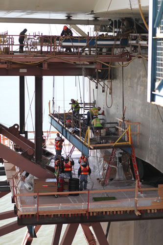Workers prepare the concrete cap beam for steel saddle installation. (Photo courtesy baybridgeinfo.org)