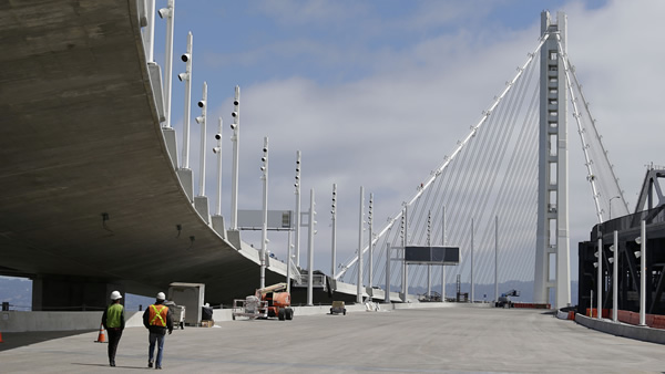 In this Thursday, Aug. 1, 2013 photo, workmen walk along the new eastern section of the San Francisco-Oakland Bay Bridge in San Francisco. Crowded roadways and packed buses, trains and ferries are on tap for commuters starting Wednesday night, Aug. 28, 2013 when officials shut down the San Francisco-Oakland Bay Bridge to traffic in preparation for a new $6.4 billion span opening late Monday, Sept. 2 or early Tuesday. (AP Photo/Eric Risberg)
