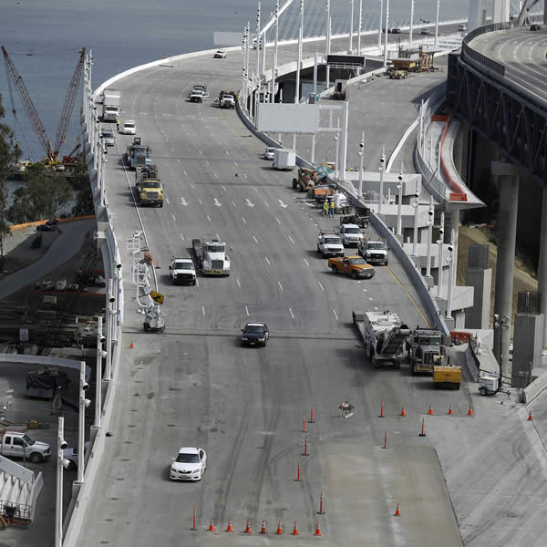 Construction crews work on the new eastern section of the San Francisco-Oakland Bay Bridge in San Francisco, Thursday, Aug. 29, 2013. Commuters faced their first morning on Thursday without the bridge, but there weren't major traffic snarls as day broke across the Bay Area. Alternate bridges to get into San Francisco were more crowded around 6:30 a.m., and Bay Area Rapid Transit trains appeared to be carrying a heavier load than usual. But commuters were managing to get around. (AP Photo/Jeff Chiu)