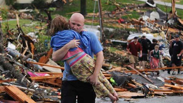 A man carries a young girl who was rescued after being trapped with her mother in their home after a tornado hit Joplin, Mo. on Sunday evening, May 22, 2011.  (AP Photo/Mike Gullett)