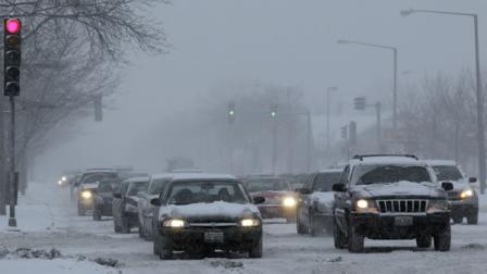Cars move slowly as snow falls in Chicago on Friday, Jan. 20, 2012.