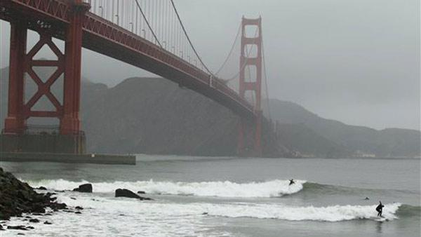 Surfers ride a pair of waves beneath the Golden Gate Bridge at Fort Point in San Francisco, Wednesday, March 14, 2012.