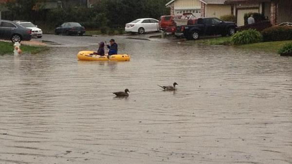 People raft down a street in East Vallejo after it floods