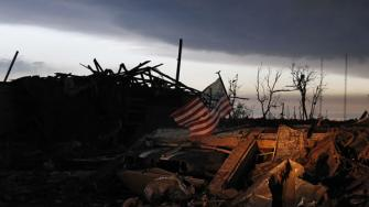 At sunrise Tuesday May 21, 2013, an American flag blows in the wind atop the rubble of a destroyed home in Moore, Okla.