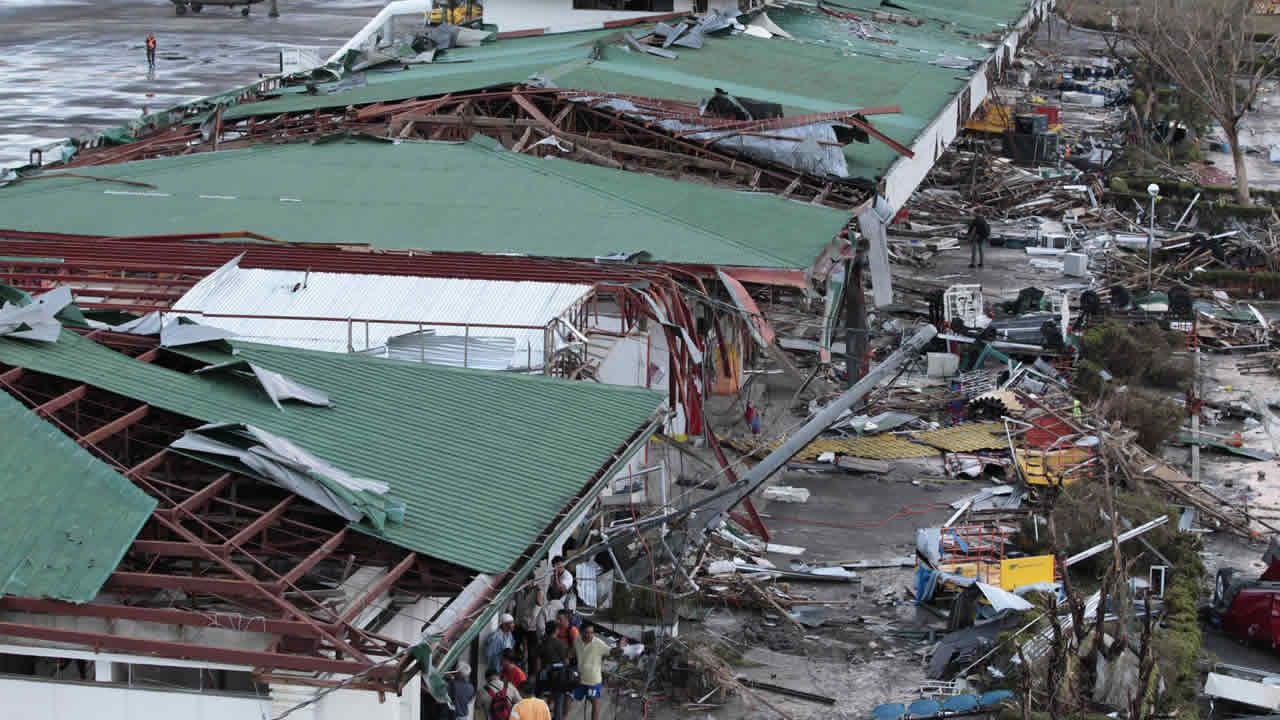 People stay outside the remains of a damaged airport terminal after powerful Typhoon Haiyan slammed into Tacloban city, Leyte province central Philippines on Saturday, Nov. 9, 2013