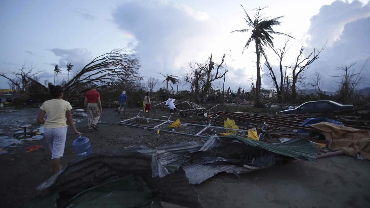 Residents walk by debris after powerful Typhoon Haiyan slammed into Tacloban city, Leyte province, central Philippines on Saturday, Nov. 9, 2013