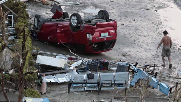 A resident passes by toppled car outside an airport terminal after powerful Typhoon Haiyan slammed into Tacloban city, Leyte province central Philippines on Saturday, Nov. 9, 2013