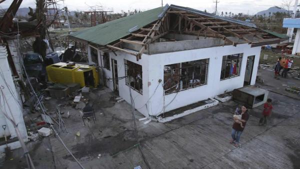 A resident passes by a damaged house after powerful Typhoon Haiyan slammed into Tacloban city, Leyte province central Philippines on Saturday, Nov. 9, 2013