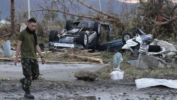 A Filipino trooper passes by toppled cars outside the airport terminal after powerful Typhoon Haiyan slammed into Tacloban city, Leyte province, central Philippines on Saturday, Nov. 9, 2013.