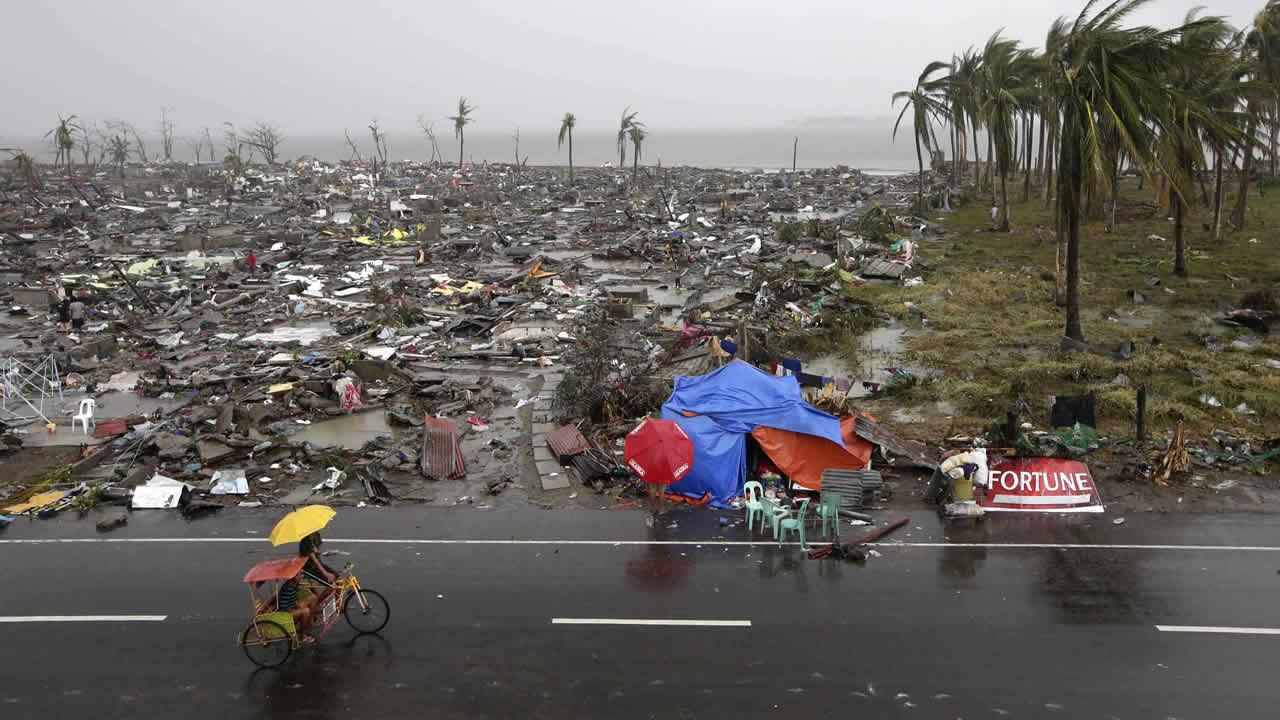 Residents walk past the devastation caused by Typhoon Haiyan, Sunday, Nov. 10, 2013, in Tacloban city, Leyte province in central Philippines.
