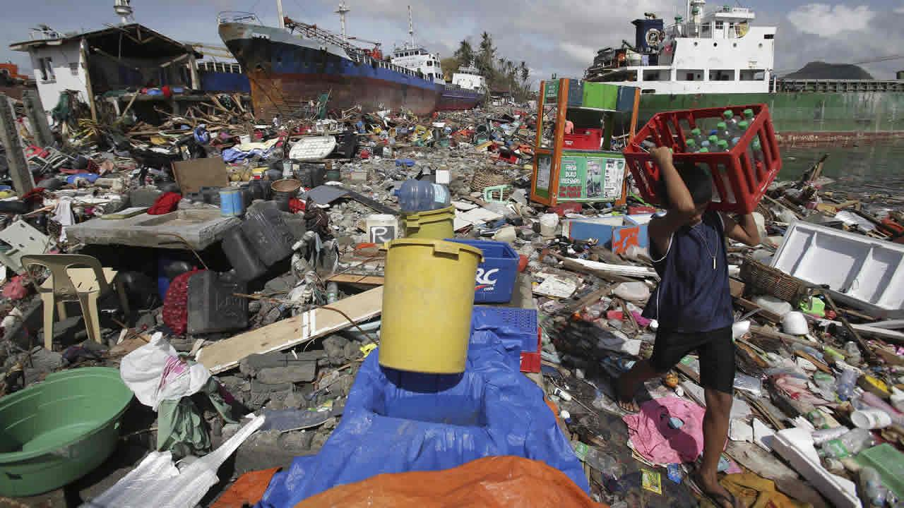 A Filipino boy carries bottled water amongst the damaged houses where a ship was washed ashore in Tacloban city, Leyte province, central Philippines on Sunday, Nov. 10, 2013.