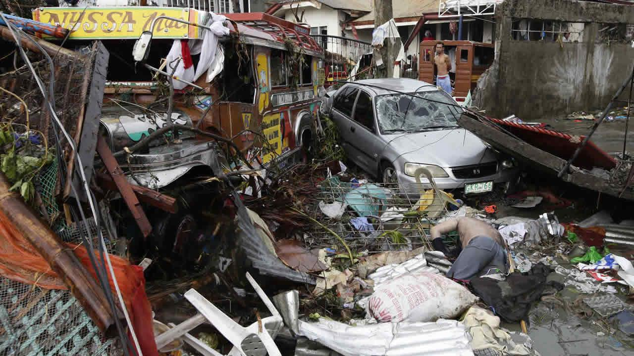 Vehicles and a body lie amongst the devastation caused by typhoon Haiyan, in Tacloban city, Leyte province central Philippines on Sunday, Nov. 10, 2013.