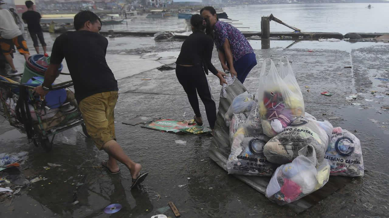 Survivors uses a steel roof to carry groceries and supplies in Tacloban city, Leyte province, central Philippines on Sunday, Nov. 10, 2013