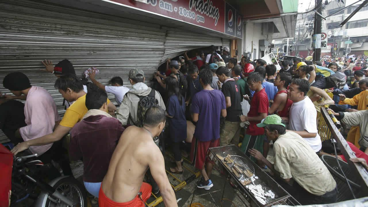Residents force open a small grocery as they start to loot in Tacloban city, Leyte province central Philippines on Sunday, Nov. 10, 2013.