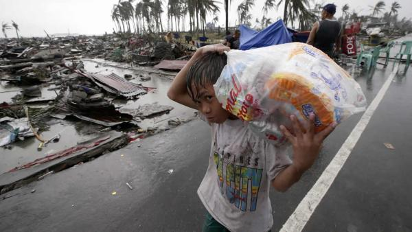 A boy carries relief goods, walking past the devastation caused by Typhoon Haiyan, in Tacloban city, Leyte province, central Philippines on Sunday, Nov. 10, 2013.