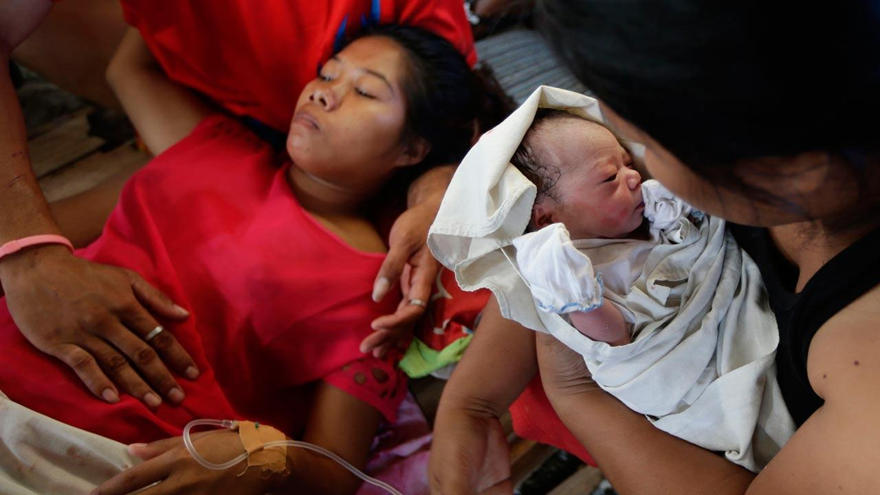 New-born baby Bea Joy is held as mother Emily Ortega, 21, rests after giving birth at an improvised clinic at Tacloban airport Monday Nov. 11, 2013 in Tacloban city, Leyte province in central Philippines.