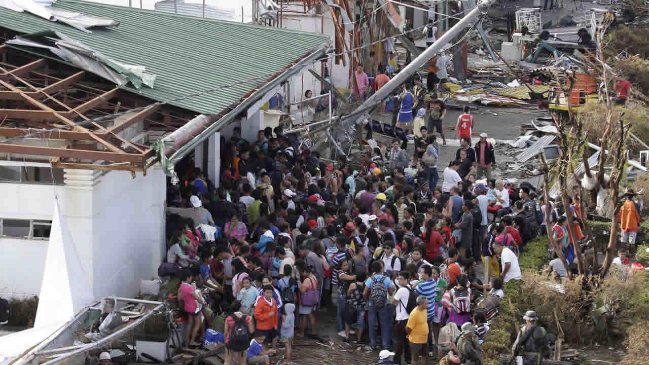 Residents watch as others throw goods from a warehouse in Guiuan, Eastern Samar province, central Philippines Monday, Nov. 11, 2013