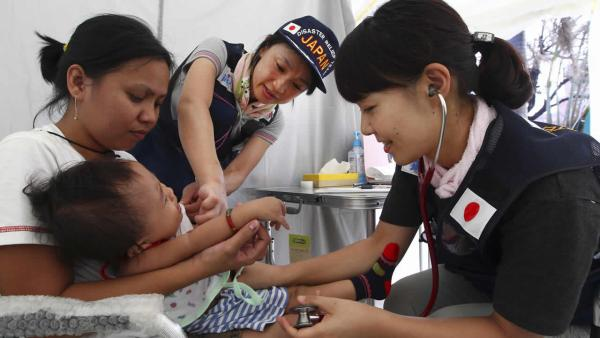 Japanese doctors examine a baby in a field hospital set up for people who are affected by Typhoon Haiyan in Tacloban, Philippines, Saturday, Nov. 16, 2013