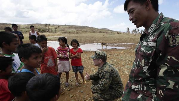 US Marine Major John Orio from San Diego, CA greets residents who were isolated by last week's super typhoon upon landing to deliver relief supplies on