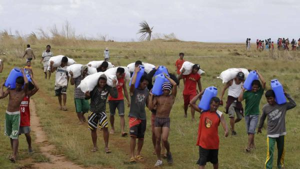 Trapped residents carry relief supplies unloaded by a U.S. Navy helicopter for villagers isolated by last week's