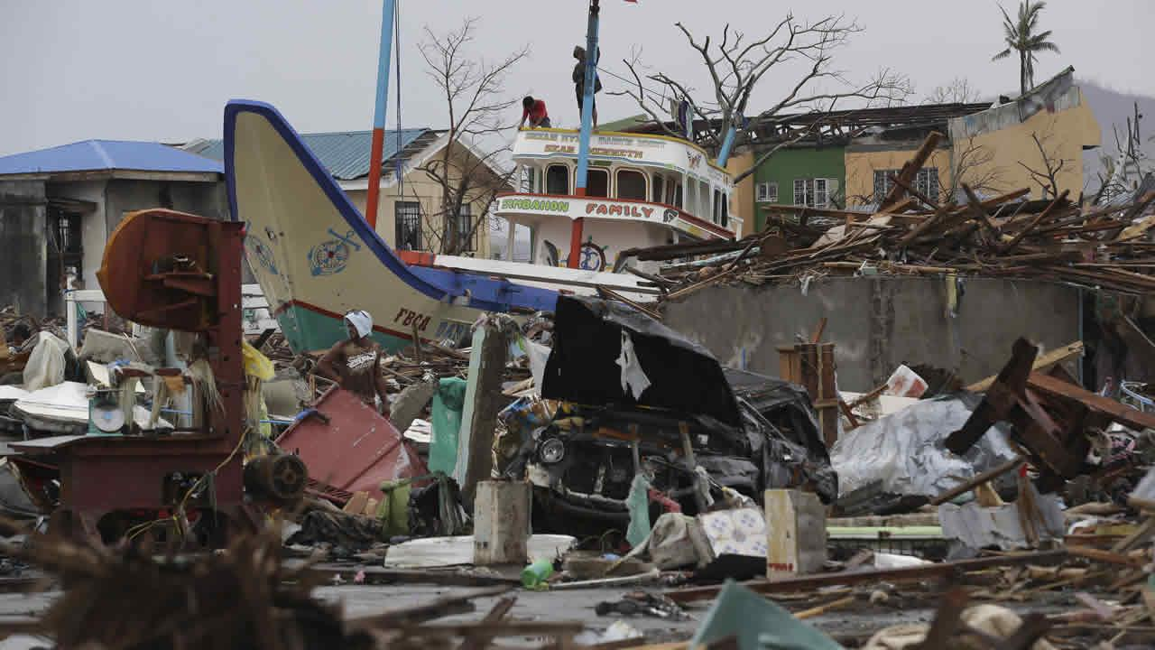 Survivors hoist a Philippine flag on top of a fishing vessel that was washed ashore at typhoon-hit Tacloban city, Leyte province, central Philippines on Saturday, Nov. 16, 2013