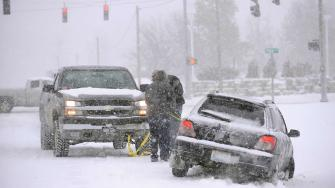 A good samaritan helps pull a motorist from the ditch on 32nd Street in Paducah, Ky., as snow fall Friday, Dec. 6, 2013. A winter mix of precipitation will continue through the day. A second winter storm is forecasted for Saturday night.