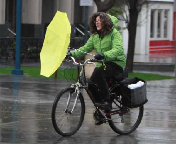 A cyclist has an umbrella malfunction while riding through the rain in downtown Sacramento, Calif., Friday, Feb. 25, 2011. Storms are sweeping through Northern California bringing rain to the Central Valley and snow in the Sierra Nevada. (AP Photo/Rich Pedroncelli)